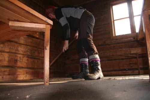 Stina sopar golvet i den gamla flottarkojan.