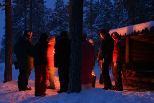 Lapplandsnattens mörker sänker sig runt lägerelden.